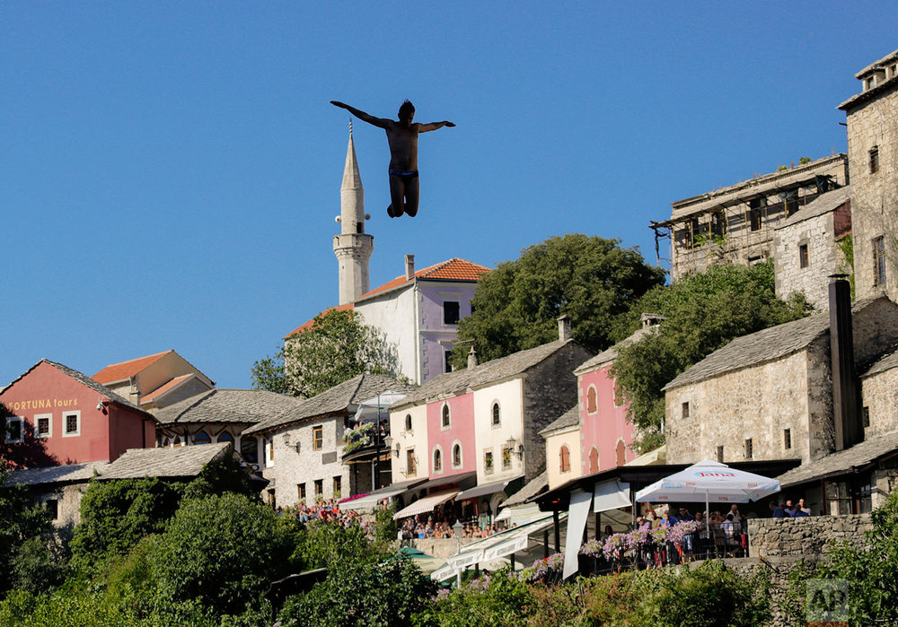 In this photograph taken on Sunday, July 30, 2017, a man jumps from the Old Bridge in Mostar, Bosnia, during an annual diving competition that has been drawing crowds for more than 4.5 centuries. (AP Photo/Amel Emric)