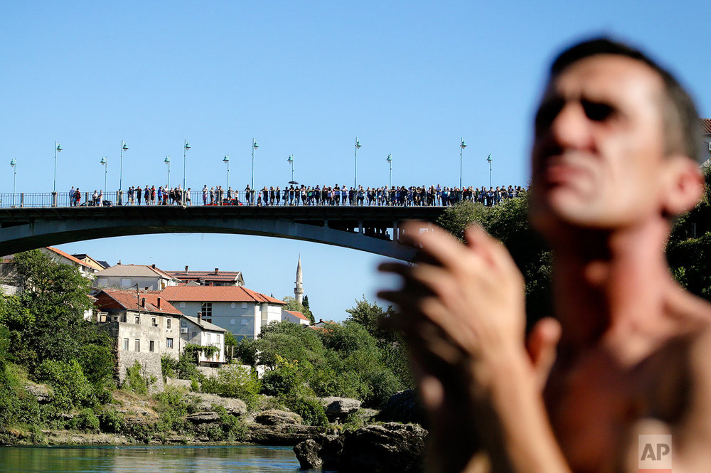 In this photograph taken on Sunday, July 30, 2017, spectators watch men jump from the Old Bridge in Mostar, Bosnia, during an annual diving competition that has been drawing crowds for more than 4.5 centuries. (AP Photo/Amel Emric)