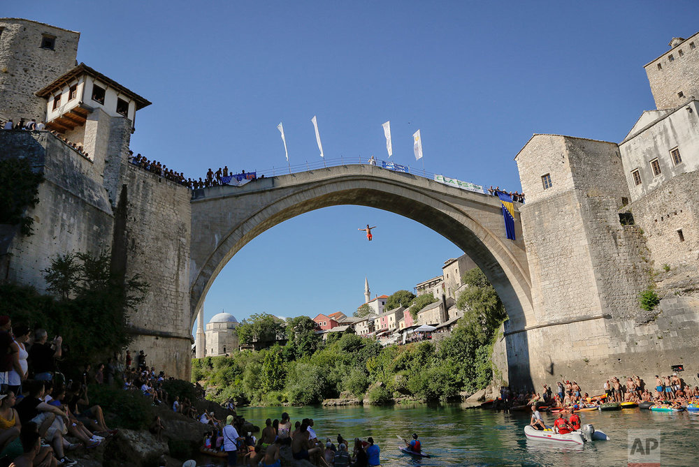 In this photograph taken on Sunday, July 30, 2017, spectators watch men jump from the Old Bridge in Mostar, Bosnia, during an annual diving competition that has been drawing crowds for more than 4.5 centuries.(AP Photo/Amel Emric)