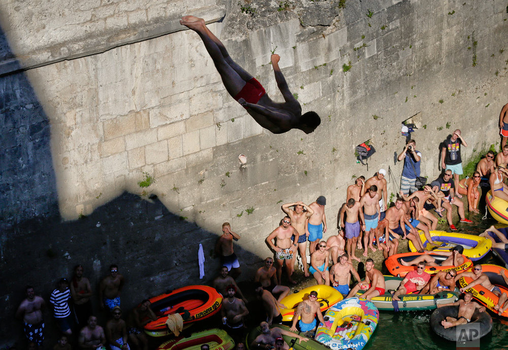 In this photograph taken on Sunday, July 30, 2017, spectators watch men dive from the Old Bridge in Mostar, Bosnia, during an annual diving competition that has been drawing crowds for more than 4.5 centuries. (AP Photo/Amel Emric)