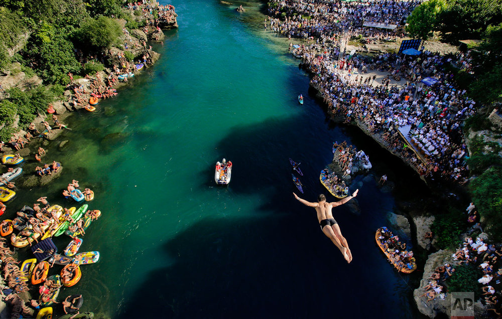 In this photograph taken on Sunday, July 30, 2017, a man dives from the Old Bridge in Mostar, Bosnia, during an annual diving competition that has been drawing crowds for more than 4.5 centuries. (AP Photo/Amel Emric)