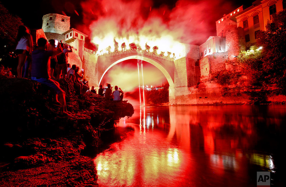 A man jumps holding torches from the Old Bridge in Mostar, Bosnia. (AP Photo/Amel Emric)