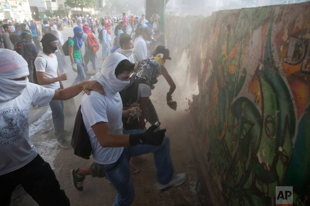 In this March 4, 2014 photo, demonstrators destroy a wall in order to have more rocks to throw at the Bolivarian National Guard during anti-government protests in Caracas, Venezuela, one year after the death of Hugo Chavez. (AP Photo/Rodrigo Abd)