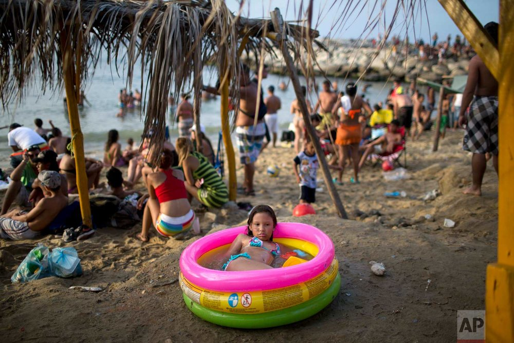 In this March 3, 2014 photo, a girl cools off in an inflatable swimming pool on the beach in La Guaira, Venezuela. (AP Photo/Rodrigo Abd)