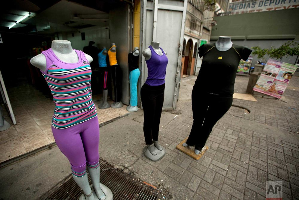 A store advertises plus size clothing, right, in downtown Caracas, Venezuela. The Venezuelan government launched a public relations campaign to halt a steady rise in obesity that, if left unchecked, threatens to lead to a costly, public health crisis. (AP Photo/Fernando Llano)