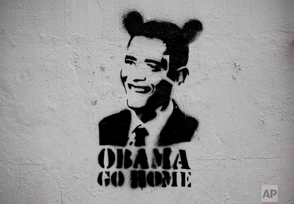 "An image of President Barack Obama wearing fake ears and the slogan ""Obama go home"" on a street wall in Caracas, Venezuela. (AP Photo/Ariana Cubillos)"