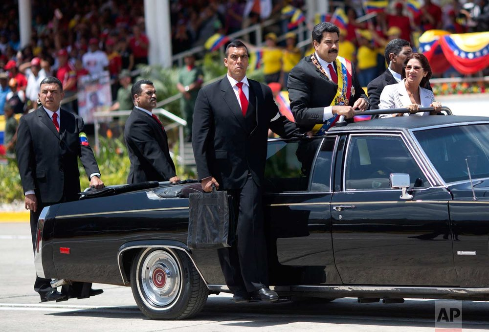 Venezuela's President Nicolas Maduro and first lady Cilia Flores are surrounded by security guards during a military parade marking the one year anniversary of the death of Venezuela's former President Hugo Chavez in Caracas, Venezuela. (AP Photo/Rodrigo Abd)