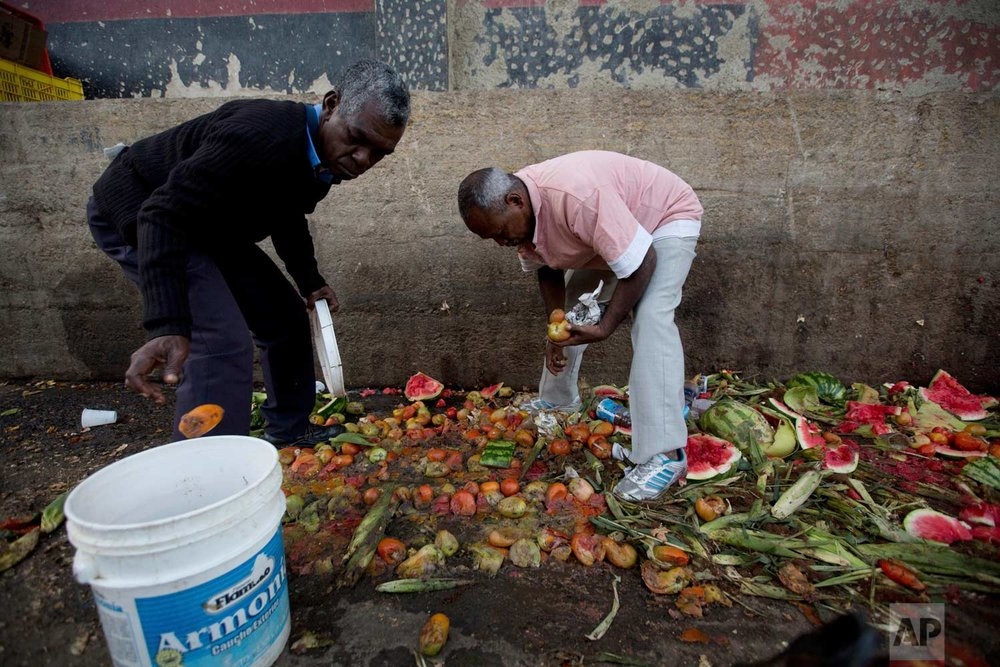 Pedro Hernandez, left, and his friend Luis Daza pick out tomatoes from the trash area of the Coche public market in Caracas, Venezuela. (AP Photo/Fernando Llano)