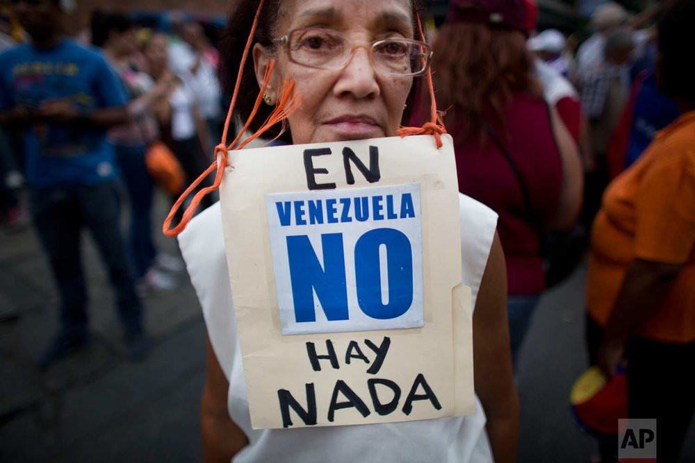 "In this Aug. 8, 2015 photo, Beatriz Silva, 74, wears a sign that reads in Spanish: ""In Venezuela, there's nothing"" as she joins a protest in Caracas, Venezuela. Anti-government protesters are denouncing food shortages and violence. (AP Photo/Ariana Cubillos)"