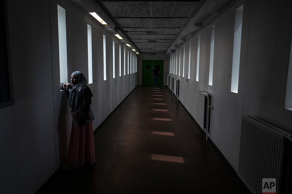 In this Thursday, July 13, 2017 photo, Ethiopian migrant Mako Husa, 40, looks out from a window of a corridor at the former prison of Bijlmerbajes in Amsterdam, Netherlands. (AP Photo/Muhammed Muheisen)