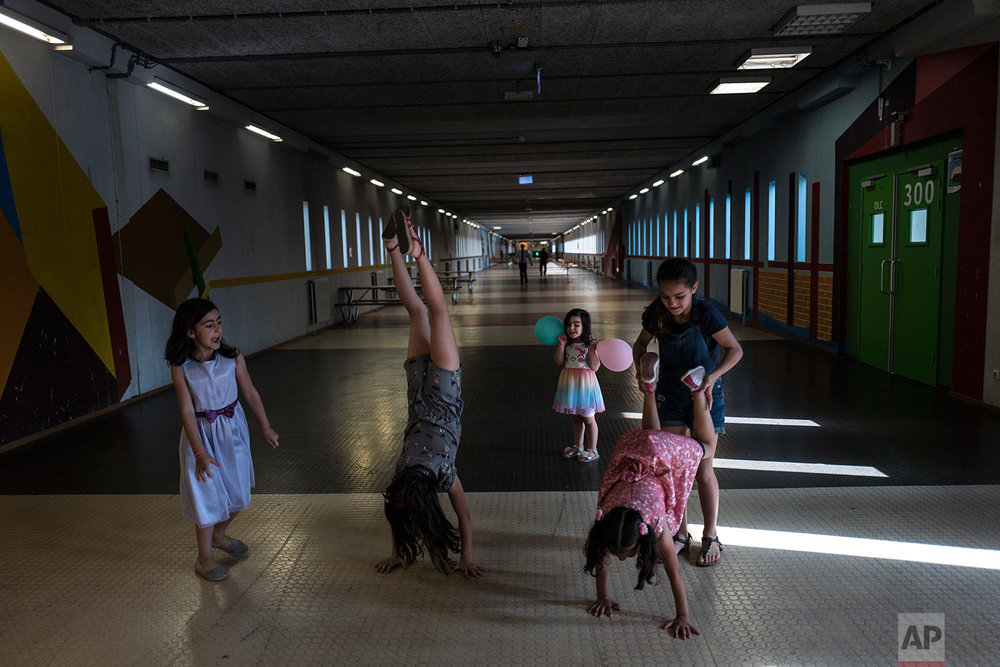 In this Wednesday, July 19, 2017 photo, Syrian refugee girls, from left, Shahd Alamar, 8, Lana Alkhawaja, 9, Maya Alamar, 4, holding balloons, Amal Sakkal, 8, and Hala Alhalaby, 8, play in a corridor known as Kalverstraat, referring to a busy shopping street in Amsterdam, at the former prison of Bijlmerbajes in Amsterdam, Netherlands. (AP Photo/Muhammed Muheisen)