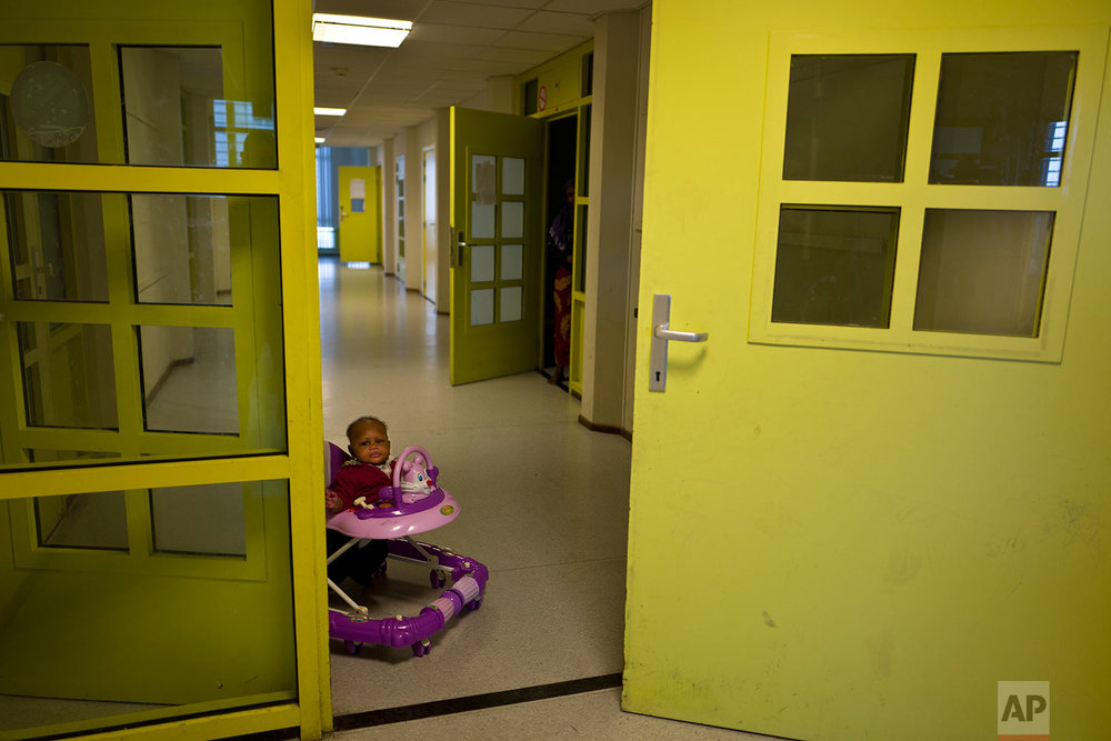 In this Tuesday, June 27, 2017 photo, Mariam Traore, an 8-month-year-old migrant from Ivory Coast, moves on a chair near her mother's room at the former prison of Bijlmerbajes, in Amsterdam, Netherlands. (AP Photo/Muhammed Muheisen)