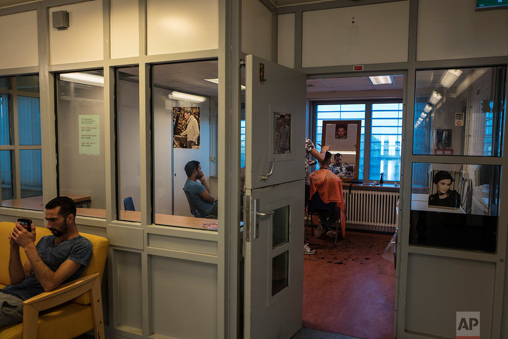 In this Friday, July 7, 2017 photo, Syrian refugee Ahmad Alshebly, 25, left, checks his mobile phone while Iranian migrant Hussein Azari, 25, is having a haircut by Iranian migrant Mohammed, 33, in a room at the former prison of Bijlmerbajes in Amsterdam, Netherlands. (AP Photo/Muhammed Muheisen)