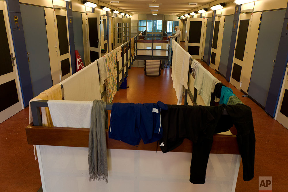 In this Thursday, June 29, 2017 photo, refugee Sondos Alnaji, 17, from Damascus, Syria, hangs her laundry outside her room at the former prison of Bijlmerbajes, in Amsterdam, Netherlands. (AP Photo/Muhammed Muheisen)