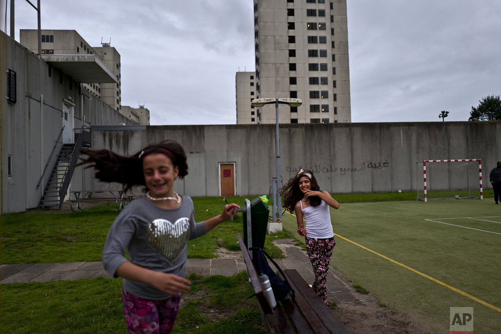In this Friday, July 28, 2017 photo, Syrian refugee girls, Mishleen Samir, 10, right, from Damascus, and her friend Claire Alzain, 10, from Damascus, run after each other while playing in a yard at the former prison of Bijlmerbajes in Amsterdam, Netherlands. (AP Photo/Muhammed Muheisen)