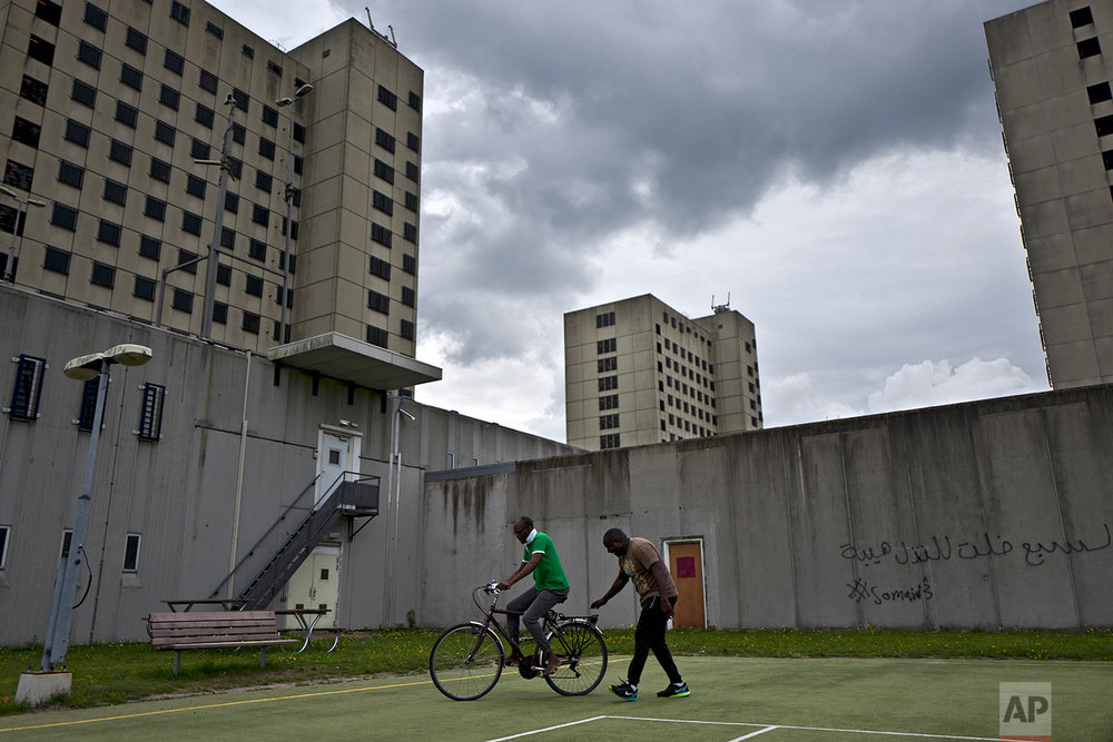 In this Monday, July 3, 2017 photo, Aimable Nasbimana, 37, right, a migrant from Burundi, teaches his Congolese friend Prosper Baseka, 37, how to ride a bicycle in a yard at the former prison of Bijlmerbajes in Amsterdam, Netherlands. (AP Photo/Muhammed Muheisen)