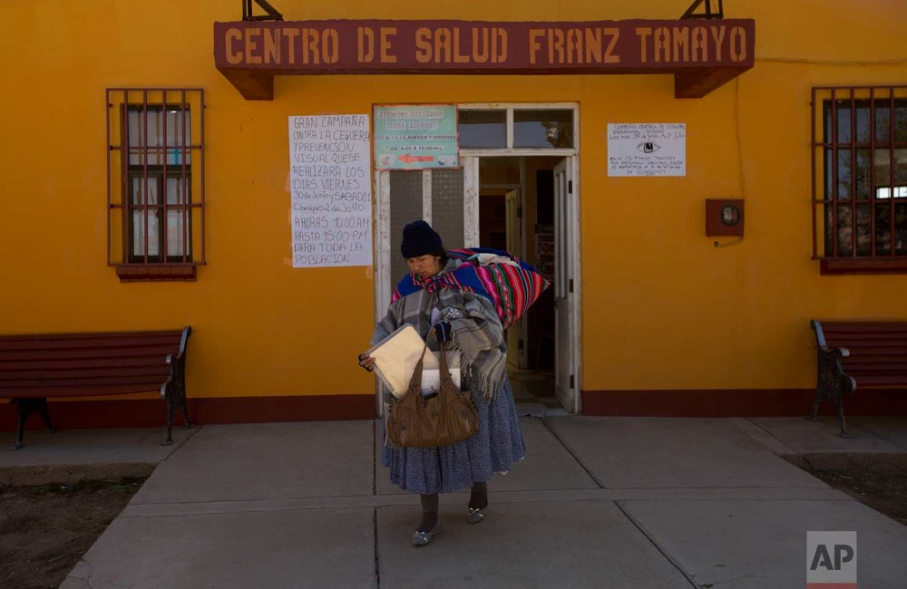 In this June 27, 2017 photo, Mariana Limachi carries her 21-day-old son Abraham Dilan, who was delivered at home by a midwife, swaddled on her back as she leaves the Franz Tamayo Medical Center where a doctor gave him a routine check-up in El Alto, Bolivia. (AP Photo/Juan Karita)