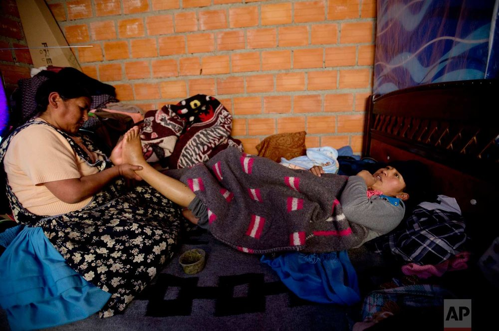 "In this June 20, 2017 photo, midwife Ana Choque massages the feet of Mariana Limachi two weeks after delivering Limachi's first child at her home in El Alto, Bolivia. Maternal deaths in Bolivia are concentrated among poor, rural indigenous women. Critics say Bolivia's public health centers and hospitals in rural areas often lack beds, doctors and medicines. ""An equally important factor is the fact that indigenous women who have managed to get to clinics have often been treated as second-class citizens, scorned because of their gender, their ethnicity and their traditions,"" the U.N. body said in a 2009 report. (AP Photo/Juan Karita)"