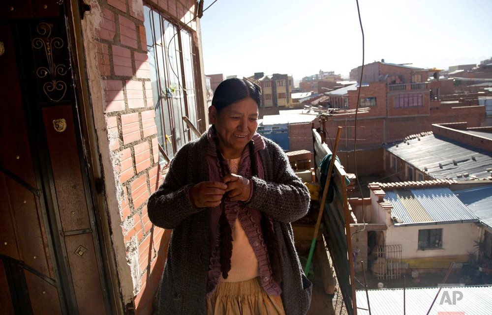 In this July 20, 2017 photo, midwife Ana Choque braids her hair after getting home from a prenatal care visit at a patient's home in El Alto, Bolivia. Choque, who began learning midwifery at age 15 from her grandmother, is one of 22 midwives who passed an exam to get qualified by the health ministry as part of a midwifery program within the public health system. (AP Photo/Juan Karita)