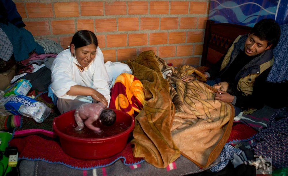 "In this June 6, 2017 photo, midwife Ana Choque bathes newborn Abraham Dilan as his parents Mariana Limachi and Wilder Chambi rest on their bed after giving birth to their first child at home in El Alto, Bolivia. ""I saw the miracle of life and that turned me into a midwife,"" Choque said. (AP Photo/Juan Karita)"