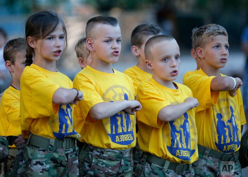 In this photo taken on Saturday, July 8, 2017, students at a paramilitary camp for children hit their fists onto their hearts during an evening ceremony outside Kiev, Ukraine. (AP Photo/Efrem Lukatsky)