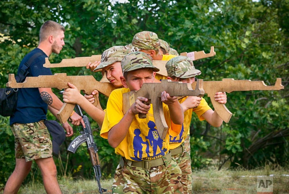 In this photo taken on Saturday, July 8, 2017, students at a paramilitary camp for children holding wooden mock-rifles with the trainer, left, with a real Kalashnikov rifle looking on outside Kiev, Ukraine. (AP Photo/Efrem Lukatsky)