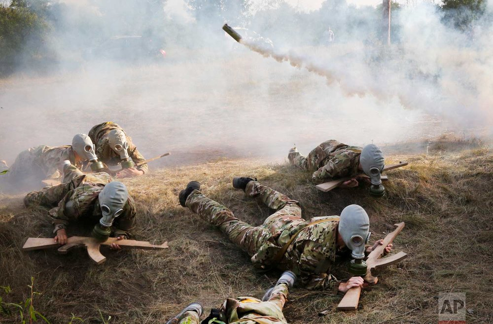 In this photo taken on Saturday, July 8, 2017, students at a paramilitary camp for children holding wooden mock-rifles work their way through an obstacle course outside Kiev, Ukraine. (AP Photo/Efrem Lukatsky)