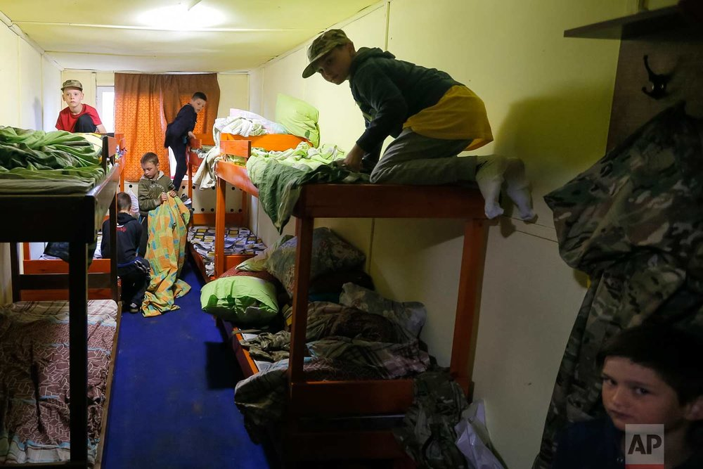 In this photo taken on Friday, July 14, 2017, students at a paramilitary camp for children train to make their beds on time outside Kiev, Ukraine. (AP Photo/Efrem Lukatsky)
