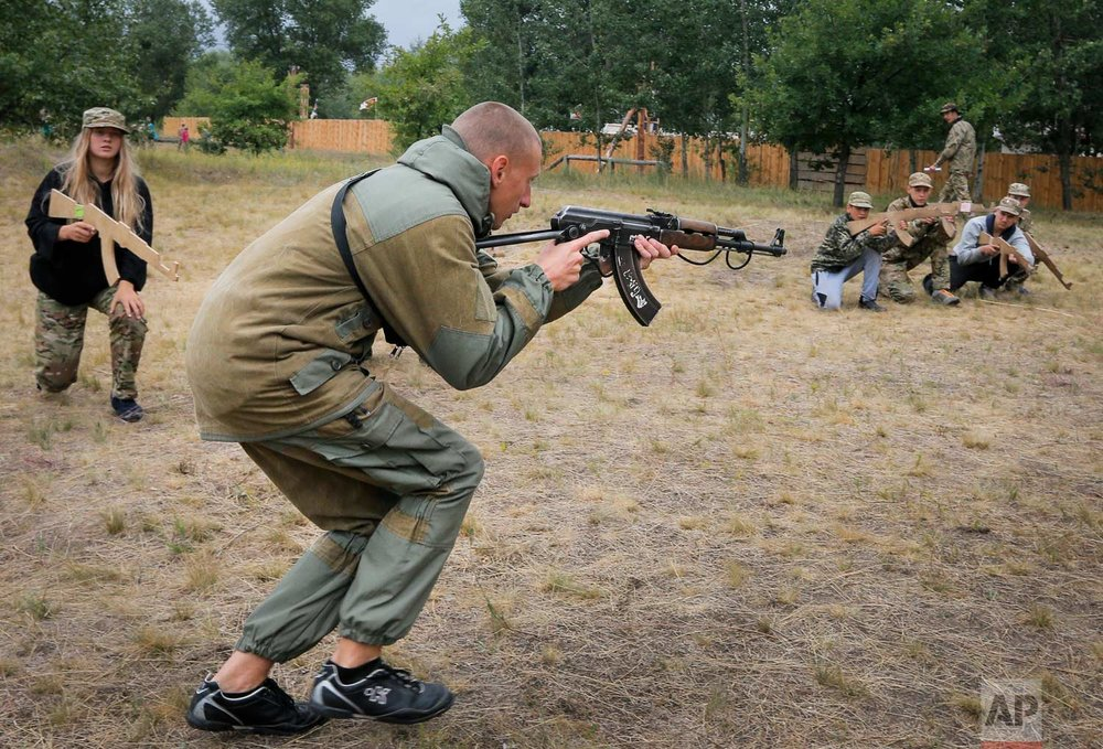In this photo taken on Friday, July 14, 2017, a trainer at a paramilitary camp for children holds a rifle during exercises outside Kiev, Ukraine. (AP Photo/Efrem Lukatsky)