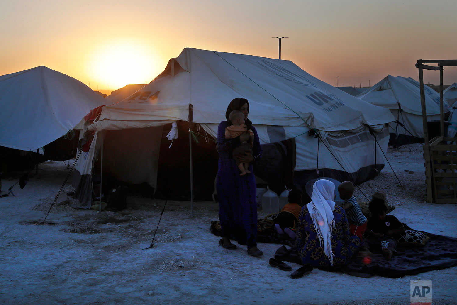 A family who fled from Raqqa the battle between U.S.-backed Syrian Democratic Forces and the Islamic State militants, sit outside their tent at a refugee camp, in Ain Issa, northeast Syria, Wednesday, July 19, 2017. (AP Photo/Hussein Malla)