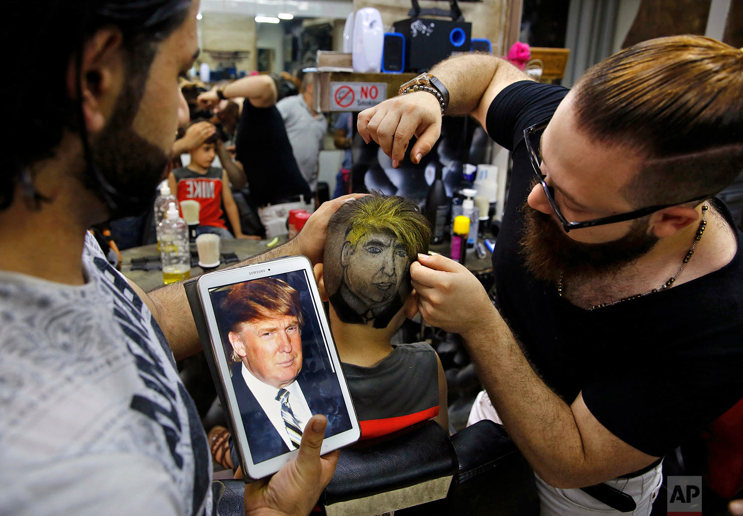 Muhannad Khaled Omar, right, prepares an image of U.S. President Donald Trump on the back of a customer's head at his barber shop in Burj al-Barajneh, southern Beirut, Lebanon on July 14, 2017. (AP Photo/Bilal Hussein)