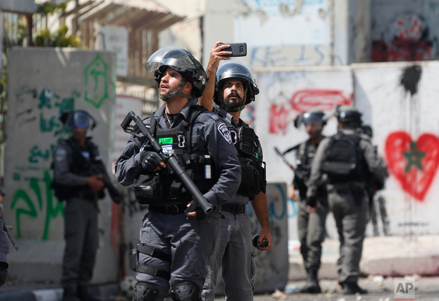An Israeli border policeman takes a selfie during clashes in the West Bank city of Bethlehem, Friday, July 21, 2017. (AP Photo/Nasser Shiyoukhi)