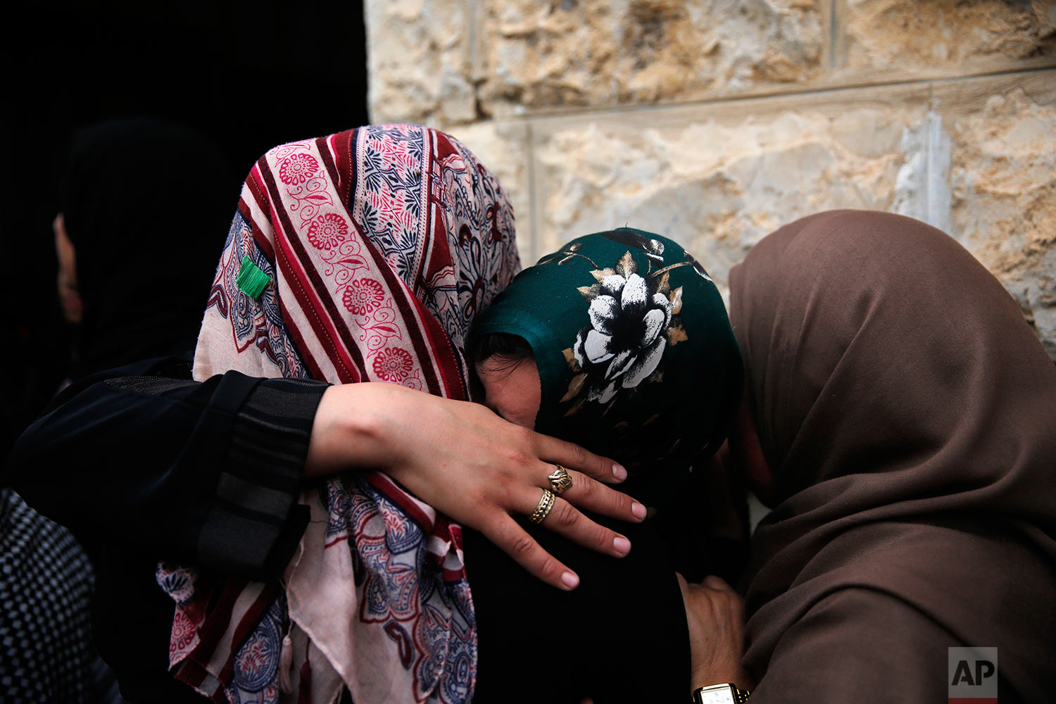 Relatives mourn during the funeral of  Mohammad Jebril in the West Bank village of Tekoa, near Bethlehem, Tuesday, July 11, 2017. Jebril was shot dead Monday after a stabbing attack against Israeli soldiers at Tekoa checkpoint. (AP Photo/Nasser Shiyoukhi).