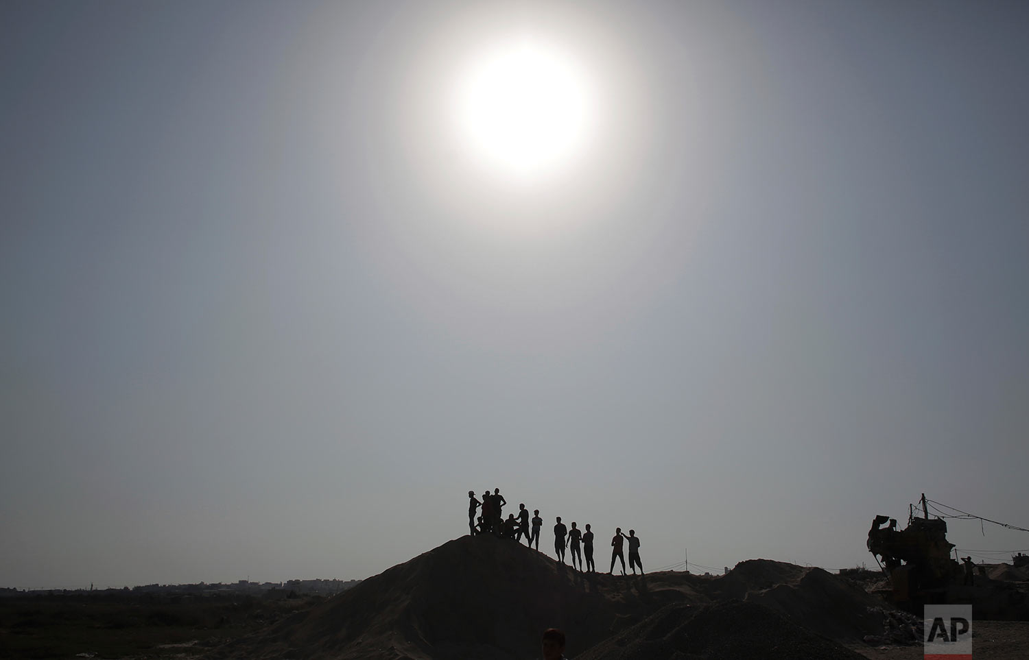 Palestinian protesters stand on top of a sandy hill during clashes with Israeli soldiers on the Israeli border with Gaza, Friday, July 21, 2017. (AP Photo/ Khalil Hamra)