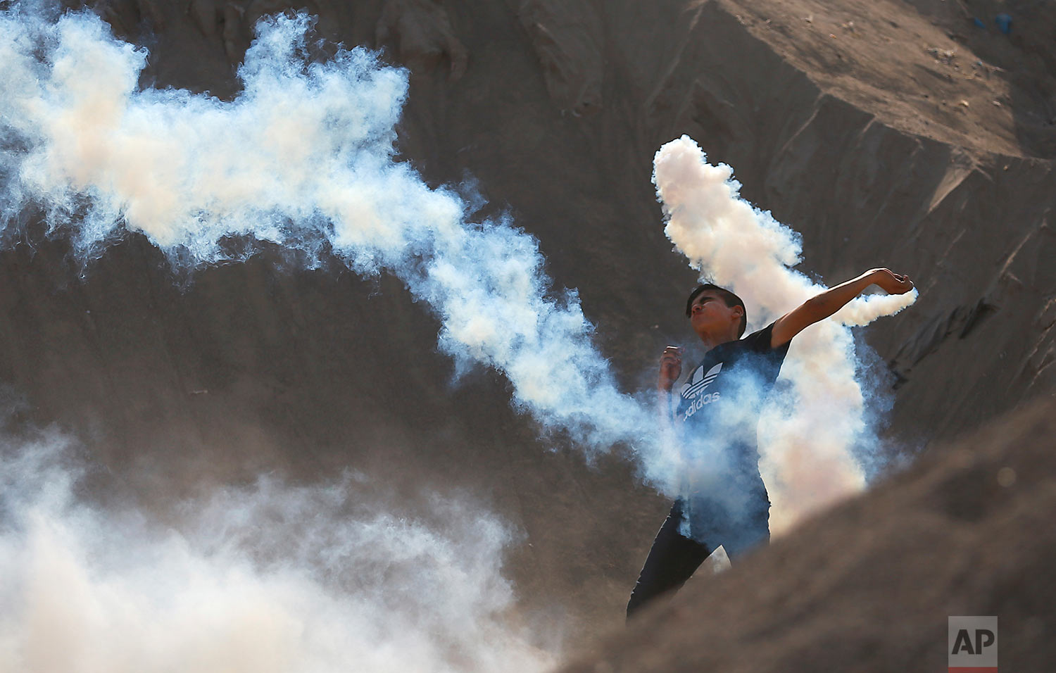 A Palestinian protester throws a teargas canister fired by Israeli soldiers back during clashes on the Israeli border with Gaza, Friday, July 21, 2017. (AP Photo/Khalil Hamra)