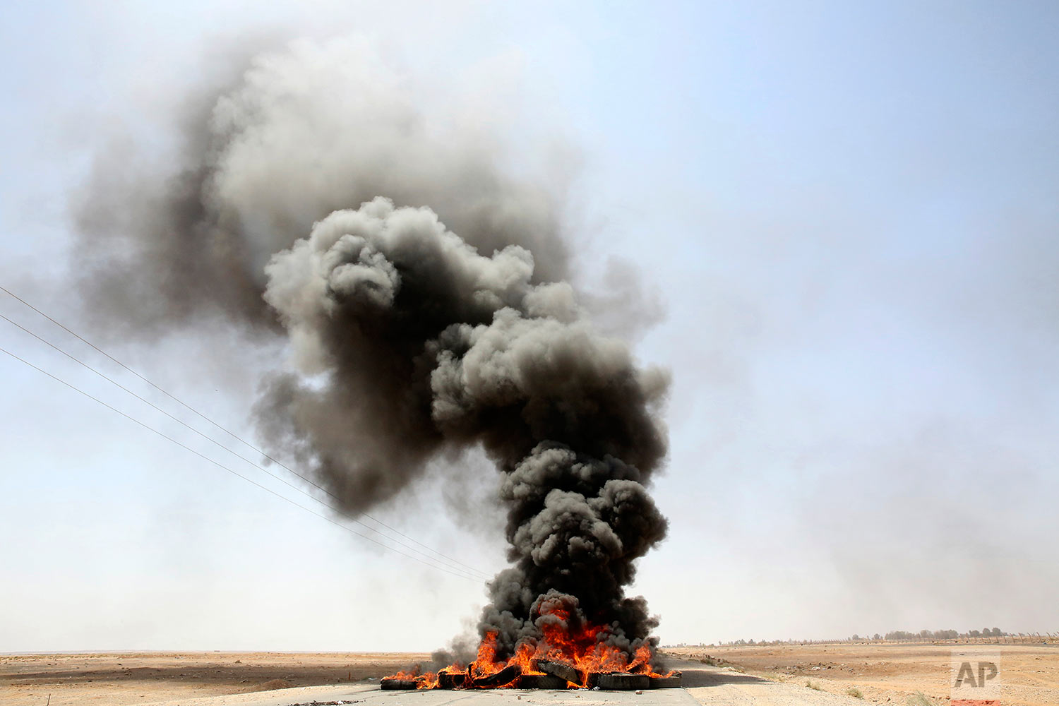 A pile of tires is seen burning on a road leading to the southern Jordanian town of al-Jafr on Tuesday, July 18, 2017. Hundreds of people in al-Jafr staged protests Tuesday following the conviction of a local soldier a day earlier in the shooting deaths of three U.S. military trainers. (AP Photo/Reem Saad)