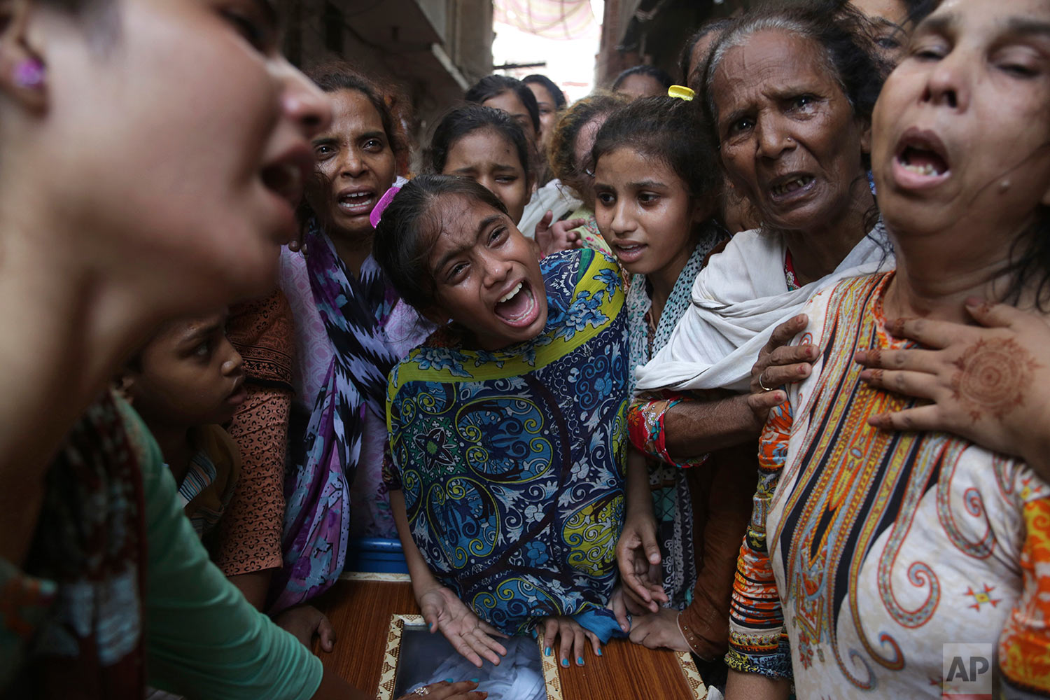 Pakistani relatives of suicide bombing victim mourn during a funeral in Lahore, Pakistan, Tuesday, July 25, 2017. (AP Photo/K.M. Chaudary)