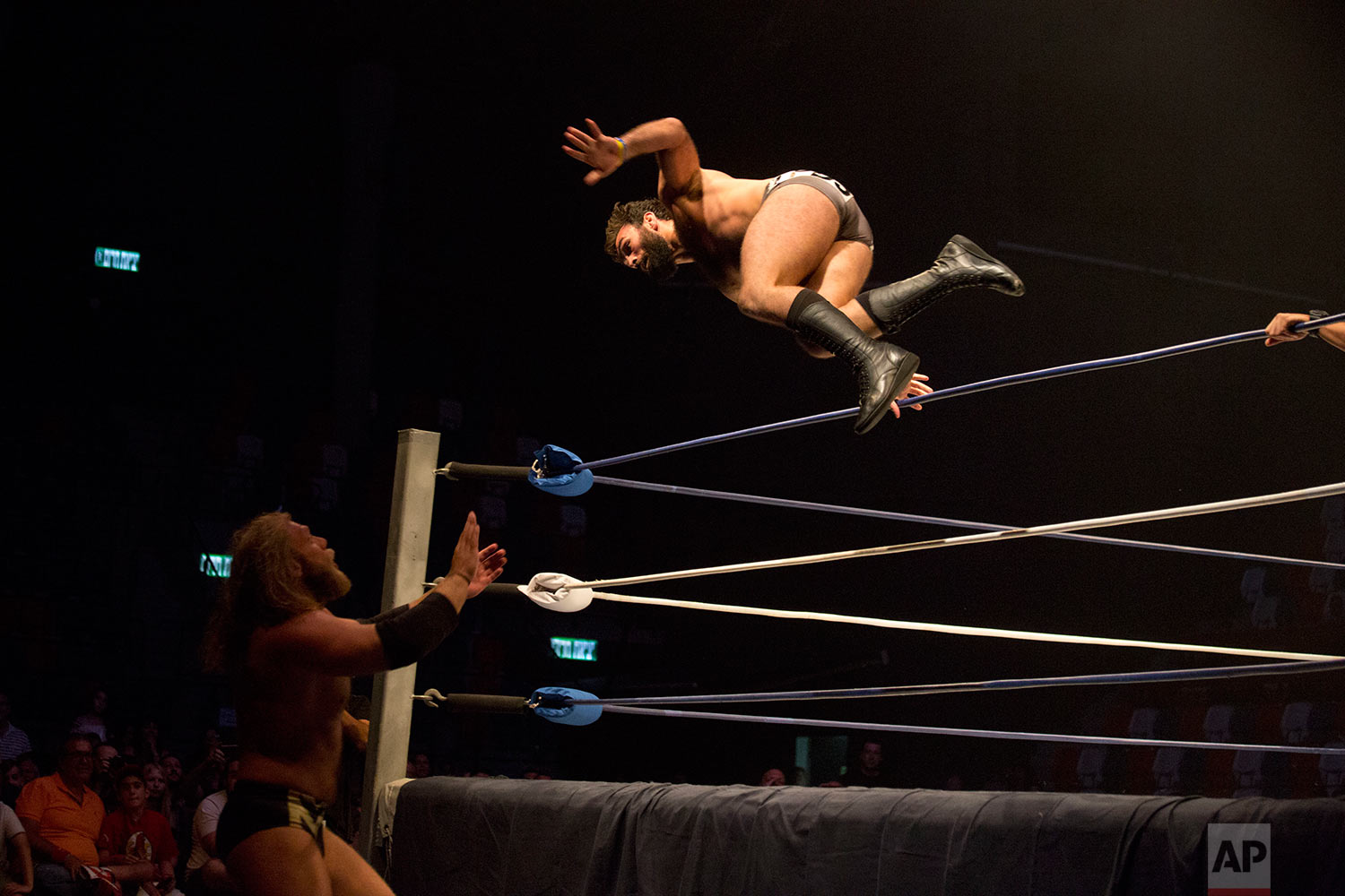 Wrestler David Starr jumps towards Juran Simmons during The Rage Wrestling Mega Show in Tel Aviv, Israel, Sunday, July 9, 2017.(AP Photo/Ariel Schalit)