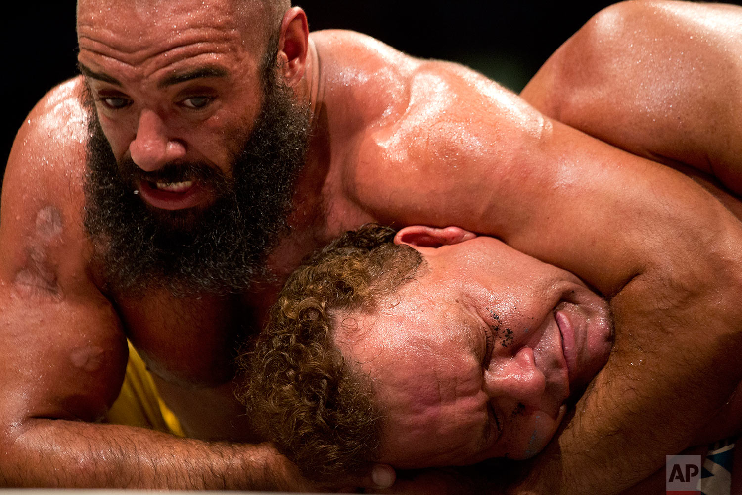 Wrestler Hakem Waqur puts a hold on Tatanka during The Rage Wrestling Mega Show in Tel Aviv, Israel, Sunday, July 9, 2017. The Israeli Wrestling League hosted a wrestling show in Tel Aviv with Kevin Von Erich and some of the WWE greatest of all time. (AP Photo/Ariel Schalit)
