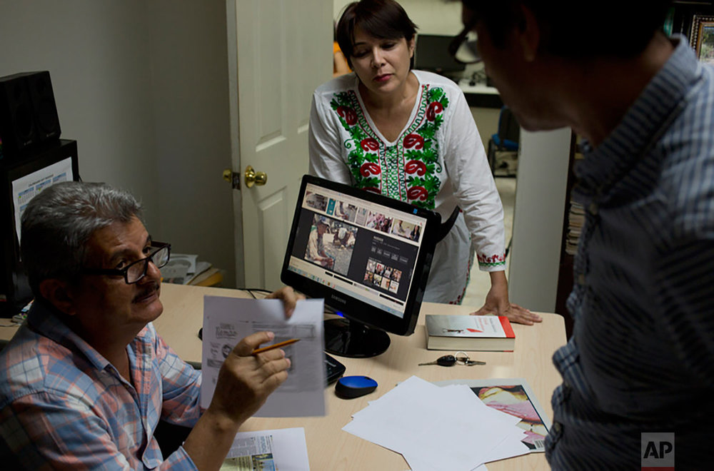 In this June 30, 2017 photo, Ismail Bojorquez, 60, co-founder and director of Riodoce, speaks with editors Andres Villareal and Judith Valenzuela as they prepare the weekly edition at his office in Culiacan, Sinaloa state, Mexico. Bojorquez is wracked with guilt for failing to protect his friend and Riodoce colleague Javier Valdez, who on May 15 was pulled from his vehicle, shot 12 times and left dead on the street. (AP Photo/Enric Marti)