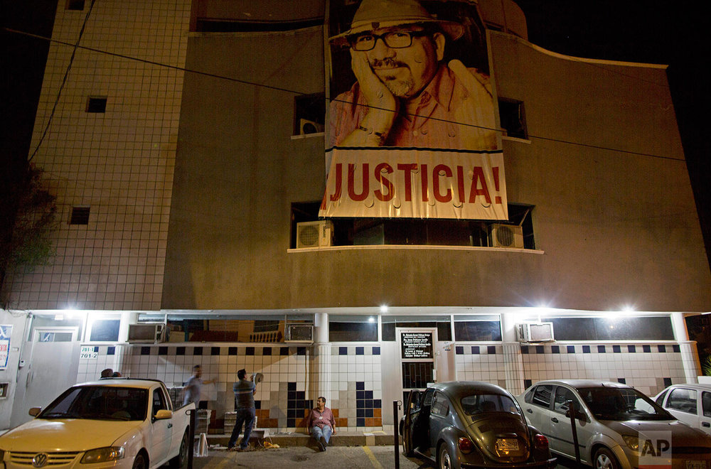 "In this July 2, 2017 photo, a banner of slain journalist Javier Valdez and the word in Spanish ""Justice!"" hangs from the Riodoce newspaper building as drivers prepare to distribute the publication in Culiacan, Sinaloa state, Mexico. In the giant photo of Riodoce's fallen founder, his middle finger is displayed defiantly for all of Sinaloa to see. (AP Photo/Enric Marti)"