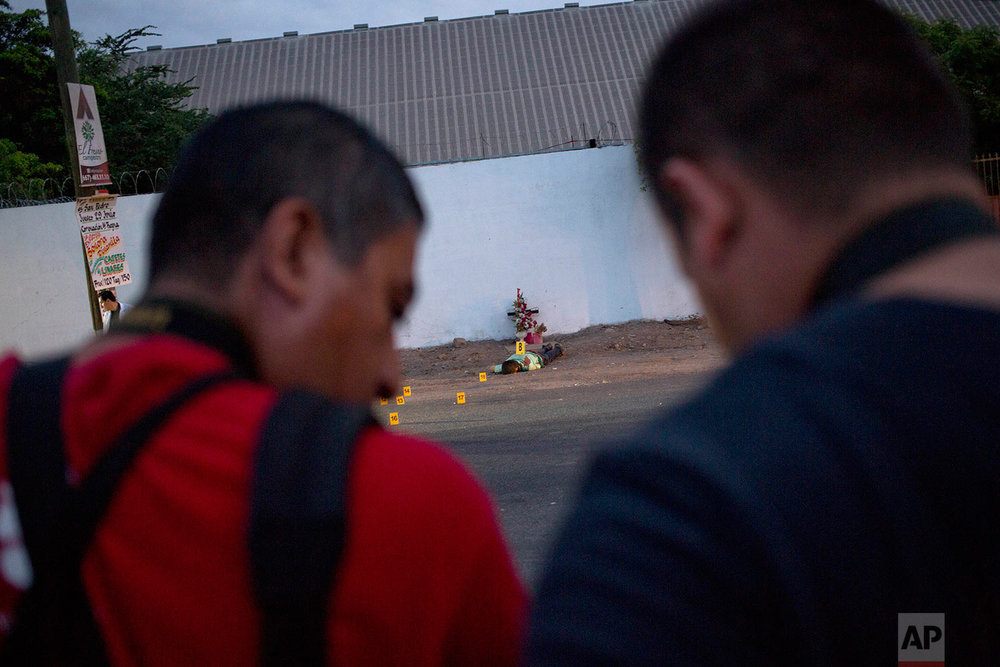 "In this June 29, 2017 photo, journalists report from the site where three bullet ridden bodies were found in Navolato, on the outskirts of Culiacan, Sinaloa state, Mexico. Sinaloa is home to the cartel of the same name that was long run by notorious kingpin Joaquin ""El Chapo"" Guzman. Since Guzman's arrest last year and extradition to the United States in January, Sinaloa has been one of the country's bloodiest battlegrounds as rival factions fight to fill the vacuum. (AP Photo/Enric Marti)"
