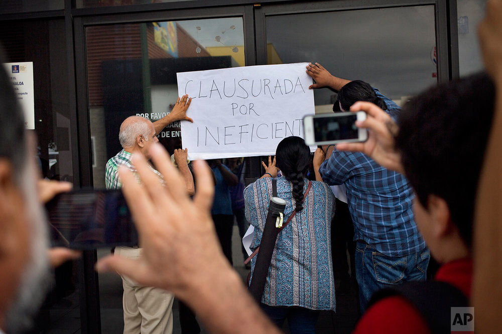 "In this June 28, 2017 photo, journalists place a sign that reads in Spanish ""closed for being inefficient"" during a demonstration at the Sinaloa state attorney's general office, after the killing of yet another journalist, in Culiacan, Sinaloa state, Mexico. The murders of journalists have had a chilling effect. Some outlets have opted to close, such as the newspaper El Norte, in the northern border state of Chihuahua, after the killing of correspondent Miroslava Breach in March. Others keep going, as El Manana of Nuevo Laredo did following the killing of its director in 2004. (AP Photo/Enric Marti)"