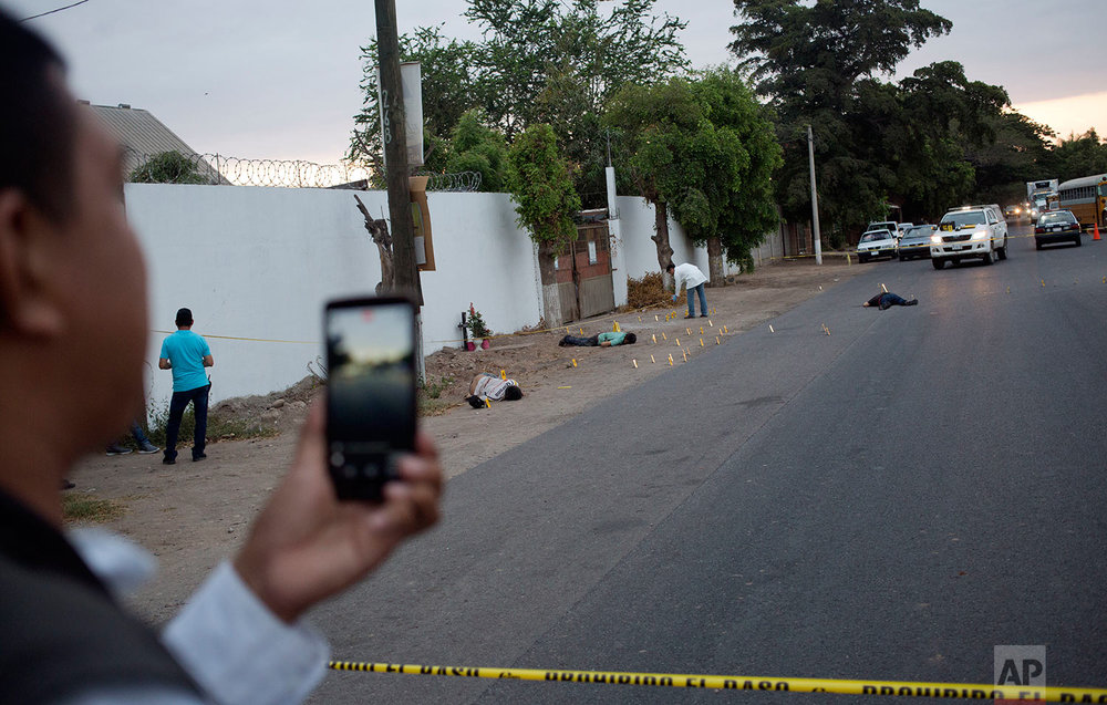 "In this June 29, 2017 photo, multimedia journalist Ernesto Martinez, known as ""El Pepis,"" from the local online news website ""Linea Directa,"" reports with his cellphone at the site where three bodies were found in Navolato, on the outskirts of Culiacan, Sinaloa state, Mexico. There are drug-traffickers, politicians, businesspeople, journalists suspected of being on the payroll of the government or the cartels, a catalog of villains who make the job of covering Mexico's chaos a daily dance of high-risk decisions. (AP Photo/Enric Marti)"
