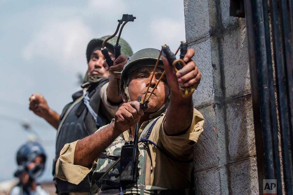 Indian paramilitary soldiers use slingshots to shoot glass marbles at Kashmiri protesters in Srinagar, Indian controlled Kashmir, Friday, Aug. 4, 2017. (AP Photo/Dar Yasin)