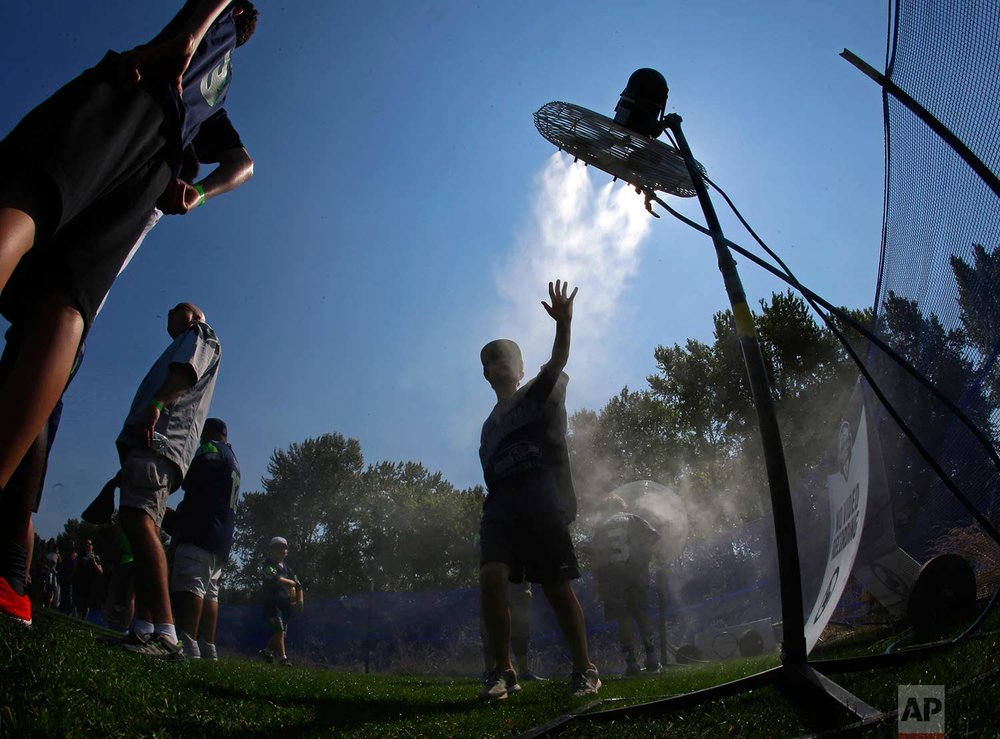 A fan attending a Seattle Seahawks NFL football training camp reaches toward a fan as he cools off at a misting station, Tuesday, Aug. 1, 2017, in Renton, Wash. (AP Photo/Ted S. Warren)