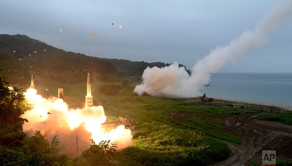 In this photo provided by South Korea Defense Ministry, South Korea's Hyunmoo II Missile system, left, and a U.S. Army Tactical Missile System, right, fire missiles during a combined military exercise between the two countries against North Korea at an undisclosed location in South Korea, Saturday, July 29, 2017. (South Korea Defense Ministry via AP)
