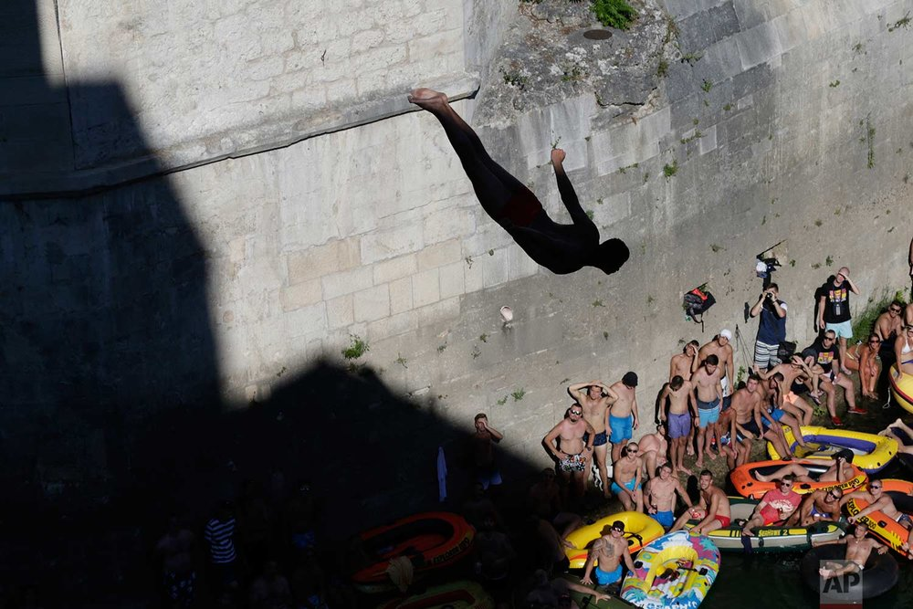 Spectators watch as a diver jumps from the Old Mostar Bridge during 451th traditional annual high diving competition, in Mostar, Bosnia, 140 kilometers (87 miles) south of the capital Sarajevo, Sunday, July 30, 2017. (AP Photo/Amel Emric)