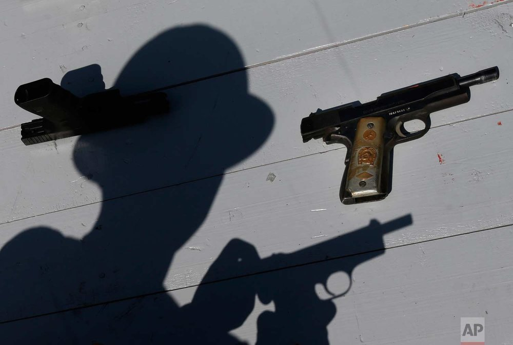 A Mexican Army soldier shows a set of hand guns sporting a gold plated grips, part of a lot of weapons slated for destruction in Mexico City, Tuesday, Aug. 1, 2017. (AP Photo/Marco Ugarte)