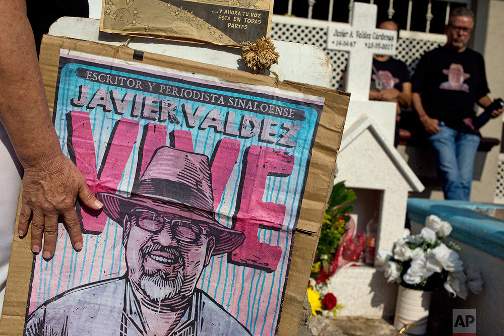 In this July 1, 2017 photo, relatives of slain journalist Javier Valdez, co-founder of Riodoce, stand at a memorial set up at the spot where he was murdered in Culiacan, Sinaloa state, Mexico. On the morning of May 15, Valdez left his Riodoce office and managed to drive just a couple of blocks before his red Toyota Corolla was stopped by two men; he was forced out of his car and shot 12 times. (AP Photo/Enric Marti)